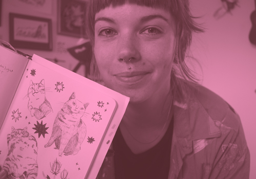 Cat illustrator and graphic designer Johanna Breuch holding up her sketchbook with cat drawings in it